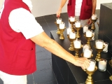 Puja House Volunteers making light offering on behalf of sponsors. -Chris