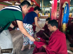 JP and Li Kim making offerings of kuyong (token monetary offering) and a portrait of His Eminence Tsem Rinpoche