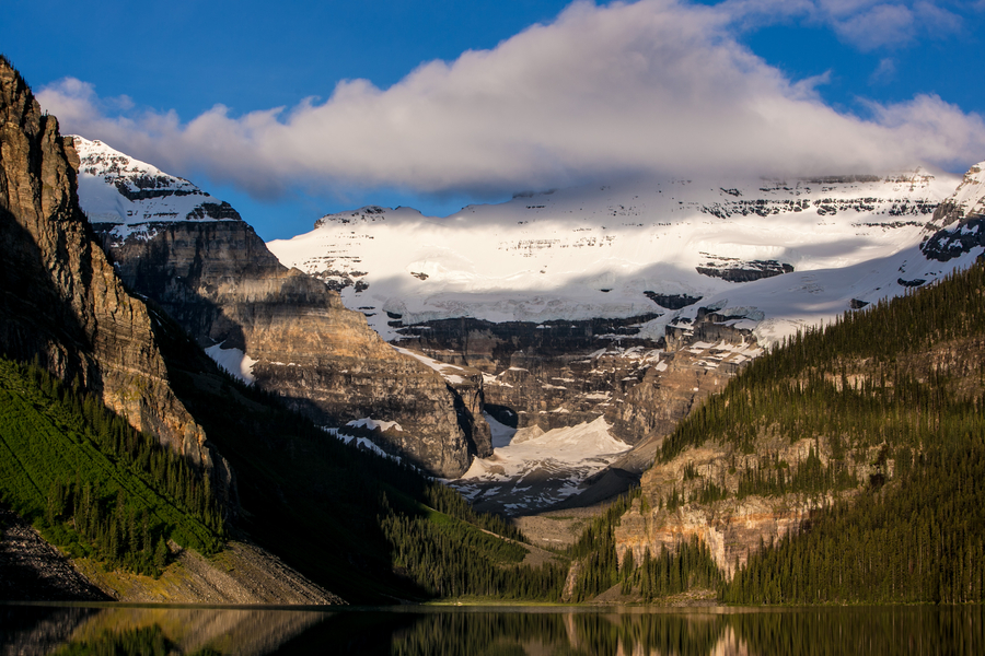The ever-changing weather conditions of Victoria Glacier and surrounding snowcapped mountains are reflected in the water of Lake Louise, Alberta, Canada. [Photo/VCG]