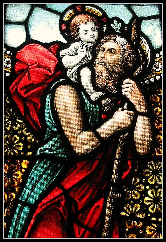Stained glass depiction of St Christopher in the Western Europe style as a man carrying the infant Jesus.