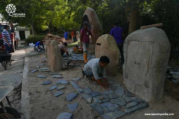 Although Medicine Buddha has been invited to his final location, the work is not over! Workers arrange a natural stone path to the stone cabinet. Click on image to enlarge.