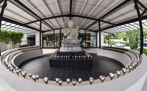 The 8-ft stone image of Lama Tsongkhapa is surrounded by many light offerings.